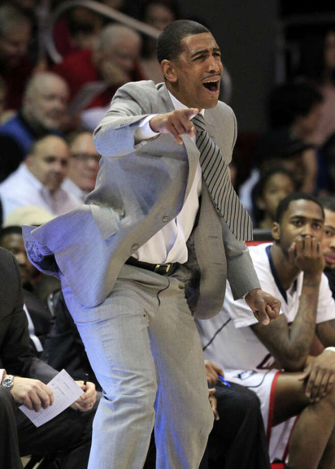 Connecticut head coach Kevin Ollie signals instructions to his team during the first half of a NCAA basketball game against SMU, Saturday, Jan. 4, 2014, in Dallas.  (AP Photo/John F. Rhodes)
