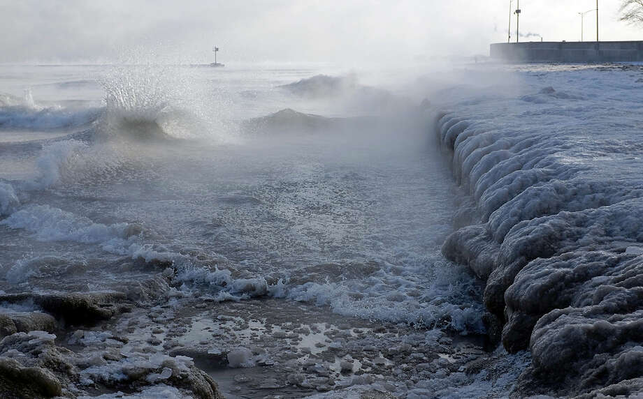 Ice forms as waves crash along Lake Michigan in below-normal temperatures near Oak Street Beach, Monday, Jan. 5, 2015, in Chicago. Forecasters expect significant snowfall and freezing temperatures this week in northern Illinois. (AP Photo/Kiichiro Sato)