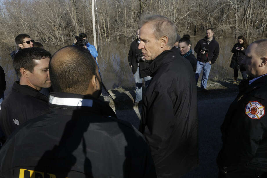 Illinois Gov. Bruce Rauner overlooks the south fork of the Sangamon River, where two teenagers were killed while crossing a flooded road last week, during his tour to the area Sunday, Jan. 3, 2016, in Kincaid, Ill. (AP Photo/Seth Perlman)