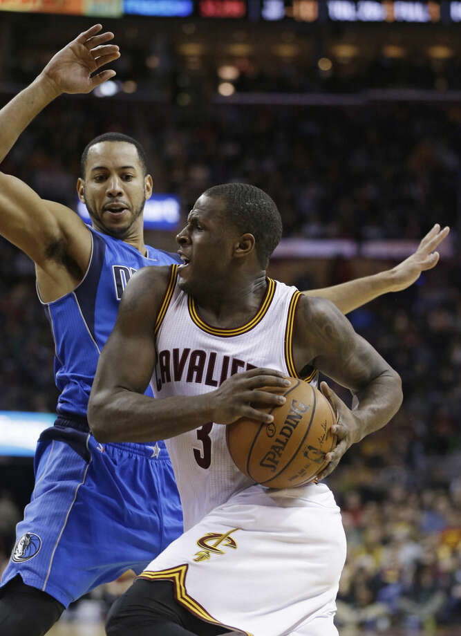 Cleveland Cavaliers' Dion Waiters, right, drives past Dallas Mavericks' Devin Harris during the second quarter of an NBA basketball game, Sunday, Jan. 4, 2015, in Cleveland. (AP Photo/Tony Dejak)