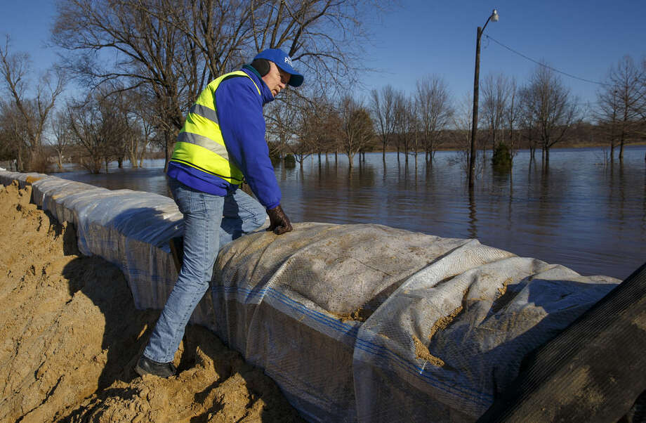 Petersburg, Ill., Mayor John Stiltz climbs the nearly 2,000-foot long wall erected to protect the town's business district from the Sangamon River on Saturday, Jan. 2, 2016. Illinois Gov. Bruce Rauner of Illinois also toured flood-ravaged areas Saturday as near-record crest predictions of the Mississippi River and levee breaks threatened more homes. (Ted Schurter/The State Journal-Register via AP) MANDATORY CREDIT
