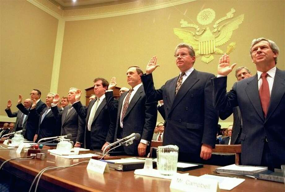 ADVANCE FOR USE SUNDAY, JAN. 5, 2014 AND THEREAFTER - FILE - In this Thursday, April 14, 1994 file photo, heads of the nation's largest cigarette companies are sworn in before a hearing of a House Energy subcommittee which was holding hearings on the contents of cigarettes on Capitol Hill in Washington. More than 40 states brought lawsuits demanding compensation for the costs of treating smoking-related illnesses. Big Tobacco settled in 1998 by agreeing to pay about $200 billion and curtail marketing of cigarettes to youths. From left are Robert Sprinkle III, executive vice president for Research American Tobacco Co.; Donald Johnston, American Tobacco; Thomas Sandefur Jr., Brown and Williamson Tobacco Corp.; Edward Horrigan Jr., Liggett Group Inc.; Andrews Tisch, Lorillard Tobacco Co.; Joseph Taddeo, U.S. Tobacco Co.; James Johnston, RJ Reynolds; and William Campbell, Phillip Morris USA. (AP Photo/John Duricka) / AP