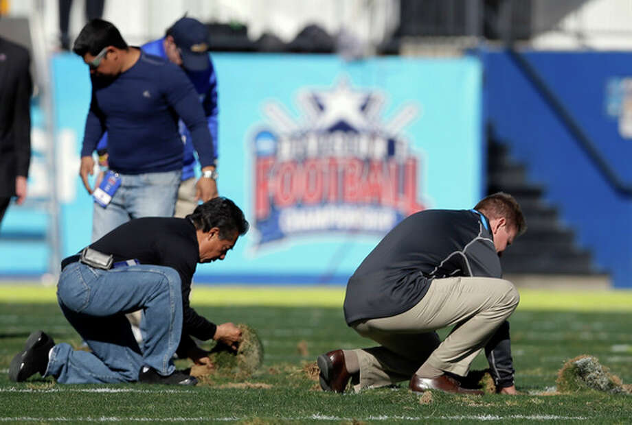 Stadium staff work on smoothing out the up-turned turf during a time out in play in the first half of the FCS championship NCAA college football game between North Dakota State and Towson, Saturday, Jan. 4, 2014, in Frisco, Texas. (AP Photo/Tony Gutierrez) / AP