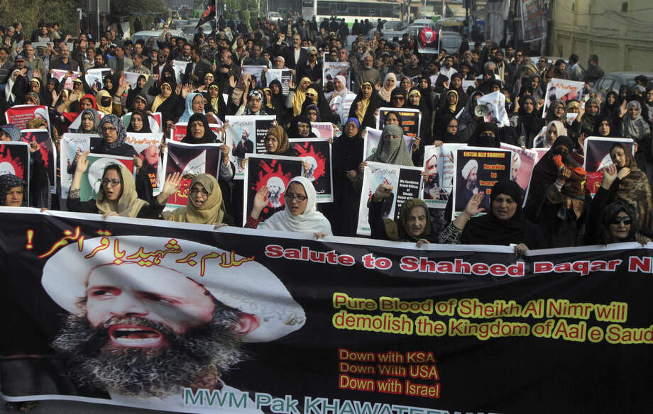 """Shiite Muslims take part in a rally to condemn the execution of Saudi Shiite cleric Sheikh Nimr al-Nimr, Sunday, Jan. 3, 2016 in Lahore, Pakistan. Saudi Arabia announced Saturday it had executed 47 prisoners convicted of terrorism charges, including al-Qaida detainees and al-Nimr, who rallied protests against the Saudi government. The placard on left reads """"we for Hussein's way and martyrdom is a pride."""" (AP Photo/K.M. Chaudary)"""