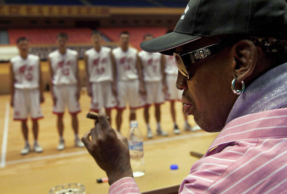 FILE - In this Dec. 20, 2013, file photo, former NBA basketball player Dennis Rodman holds a cigar as he speaks to North Korean basketball players during a practice session in Pyongyang, North Korea. During the session, Rodman selected the members of the North Korean team who will play in Pyongyang against visiting NBA stars on Jan. 8, 2014, the birthday of North Korean leader Kim Jong Un. Rodman has named a team of former NBA players to participate in an exhibition basketball game in Pyongyang, North Korea. Rodman will lead a team that includes former NBA All-Stars Kenny Anderson, Cliff Robinson, and Vin Baker. Craig Hodges, Doug Christie and Charles D. Smith are on the team, as well. (AP Photo/David Guttenfelder, File) / AP