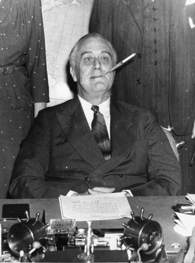 "ADVANCE FOR USE SUNDAY, JAN. 5, 2014 AND THEREAFTER - FILE - In this March 4, 1943 file photo, President Franklin D. Roosevelt poses for photographers with a cigarette in his mouth as he started his 11th year in the White House. He said, ""Let's make one this way, boys."" On Jan. 11, 1964, U.S. Surgeon General Luther Terry released an emphatic and authoritative report that said smoking causes illness and death - and the government should do something about it. (AP Photo)"