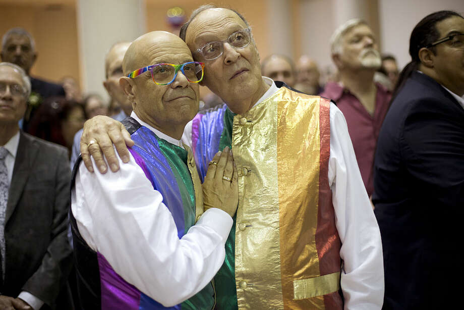 John and Shel Goldstein hug during the group wedding Tuesday, Jan. 6, 2015 in Delray Beach, Fla. About 100 couples were married in the ceremony. Florida's ban on same-sex marriage ended statewide at the stroke of midnight Monday, Jan. 5, and court clerks in some Florida counties wasted no time, issuing marriage licenses overnight to same-sex couples. But they still were beaten to the punch by a Miami judge who found no need to wait until the statewide ban expired. (AP Photo/J Pat Carter)