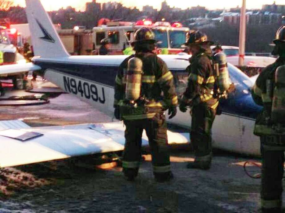 In this photo downloaded from the New York City Fire Department's Twitter account, firefighters stand near a light airplane that made an emergency landing on the Major Deegan Expressway in the Bronx borough of New York, Saturday, Jan. 4, 2014. Fire officials say all were taken to a hospital, but there have been no immediate reports of serious injuries. (AP Photo/New York City Fire Department) / FDNY