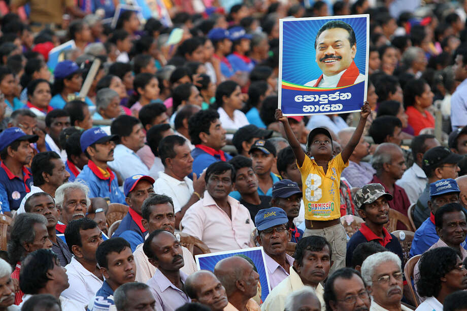 "A young supporter holds high a poster of Sri Lankan President Mahinda Rajapaksa during Rajapaksa's final public rally for the presidential elections in Kesbewa, about 20 kilometers (12 miles) southeast of Colombo, Sri Lanka, Monday, Jan. 5, 2015. A confident Rajapaksa had called the election two years ahead of schedule, hoping to win a third six-year term before voters' memories faded of the defeat of the Tamil Tiger rebels. But an internal revolt now threatens his hold on power with Health Minister Maithripala Sirisena, a close Rajapaksa aide and No. 2 in the president's Freedom Party, defecting and announcing he would run as an opposition candidate in Thursday's election. Poster reads ""Leader of the common."" (AP Photo/Sanka Gayashan)"