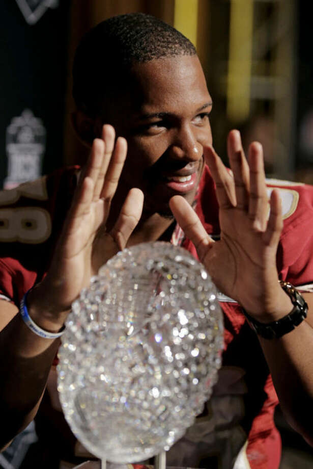 Florida State's Jonathan Akanbi poses with the Coaches' Trophy during media day for the NCAA BCS National Championship college football game Saturday, Jan. 4, 2014, in Newport Beach, Calif. Florida State plays Auburn on Monday, Jan. 6, 2014. (AP Photo/Chris Carlson)
