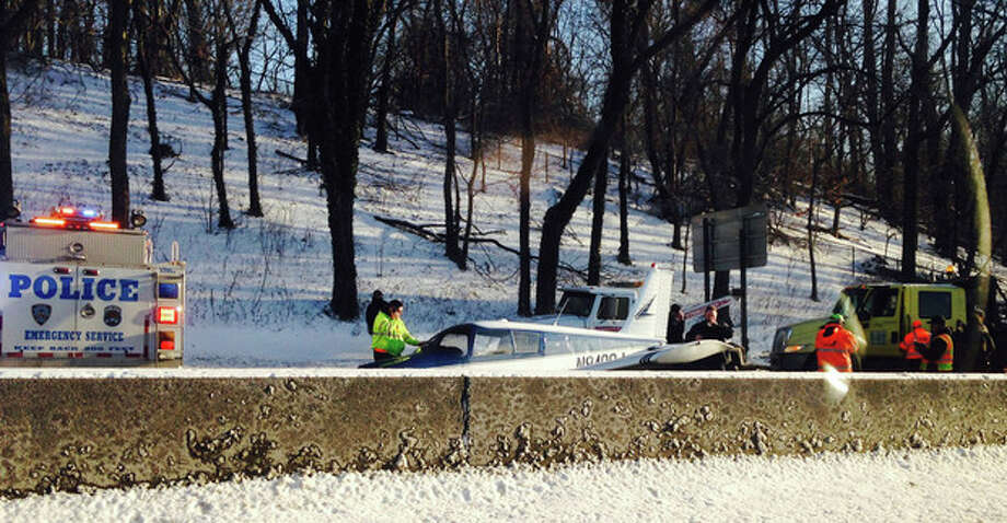 In this photo provided by Patricia Sapol, emergency personnel respond to a light airplane that made an emergency landing on the Major Deegan Expressway in the Bronx borough of New York, Saturday, Jan. 4, 2014. No major injuries were reported but northbound traffic was halted as fuel was removed from the aircraft before it could be removed from the highway. (AP Photo/Patricia Sapol) / Patricia Sapol