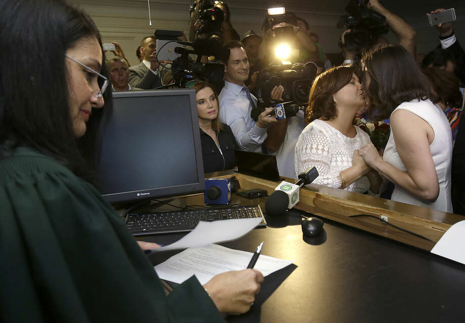 Catherina Pareto, right, and Karla Arguello, second from right, kiss after they were married by Circuit Court Judge Sarah Zabel, left, Monday, Jan. 5, 2015, in Miami. Zabel provided a jump-start Monday to Florida's entry as the 36th state where gays and lesbians can legally marry, saying she saw no reason why same-sex couples couldn't immediately get their licenses in Miami-Dade County ahead of a midnight launch statewide. (AP Photo/Wilfredo Lee)