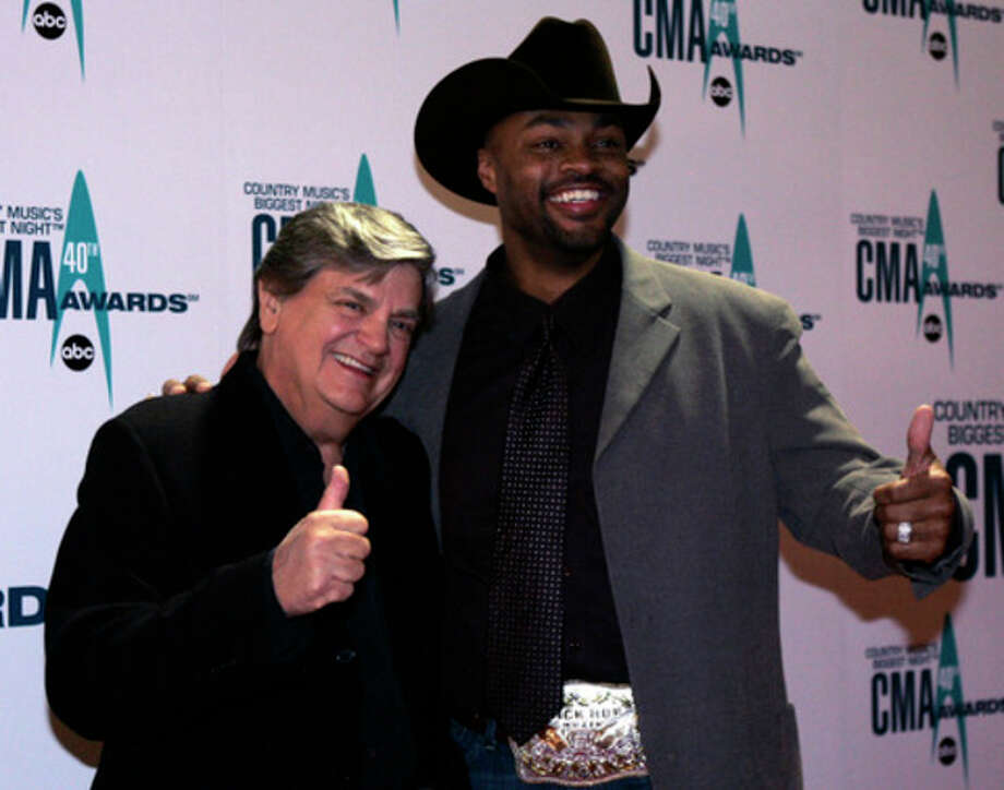FILE - In this Nov. 6, 2006 file photo, Phil Everly, left, and Cowboy Troy arrive at the 40th Annual CMA Awards in Nashville, Tenn. Everly, who with his brother Don formed an influential harmony duo that touched the hearts and sparked the imaginations of rock 'n' roll singers for decades, including the Beatles and Bob Dylan, died Friday, Jan. 3, 2014. He was 74. Everly died of chronic obstructive pulmonary disease at a Burbank hospital, said his son Jason Everly. (AP Photo/Chitose Suzuki, File) / AP