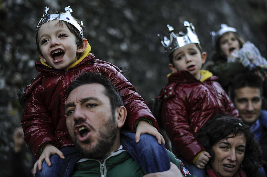 EDS NOTE : SPANISH LAW REQUIRES THAT THE FACES OF MINORS ARE MASKED IN PUBLICATIONS WITHIN SPAIN. People enjoy the Cabalgata Los Reyes Magos (Cavalcade of the three kings) the day before Epiphany, in Pamplona, northern Spain, Monday, Jan. 5, 2015. It is a parade symbolizing the coming of the Magi to Bethlehem following the birth of Jesus. In Spain and many Latin American countries Epiphany is the day when gifts are exchanged. (AP Photo/Alvaro Barrientos)