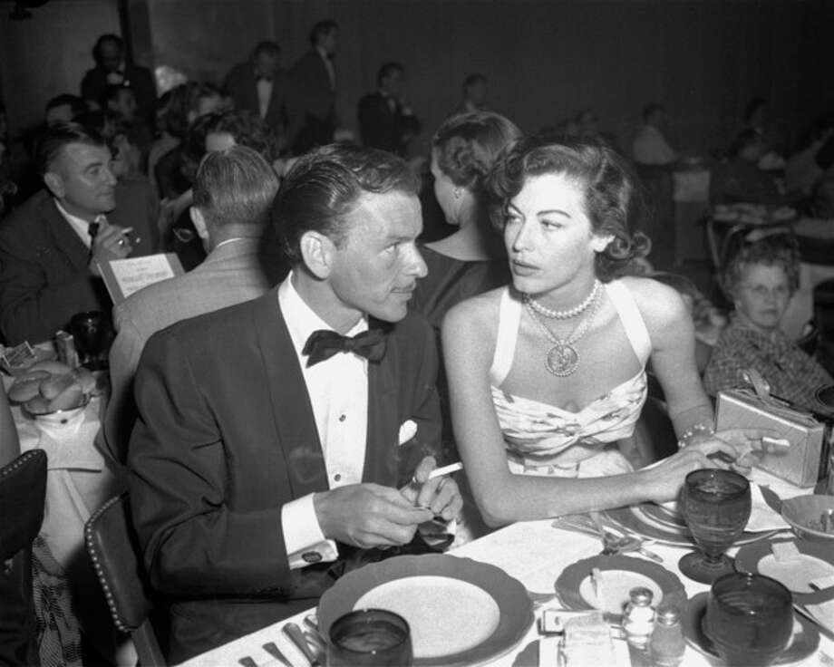 ADVANCE FOR USE SUNDAY, JAN. 5, 2014 AND THEREAFTER - FILE - In this Aug. 19, 1951 file photo, singer Frank Sinatra and Ava Gardner hold cigarettes as they dine together at the Riverside Hotel in Reno, Nev. On Jan. 11, 1964, U.S. Surgeon General Luther Terry released an emphatic and authoritative report that said smoking causes illness and death - and the government should do something about it. (AP Photo) / AP