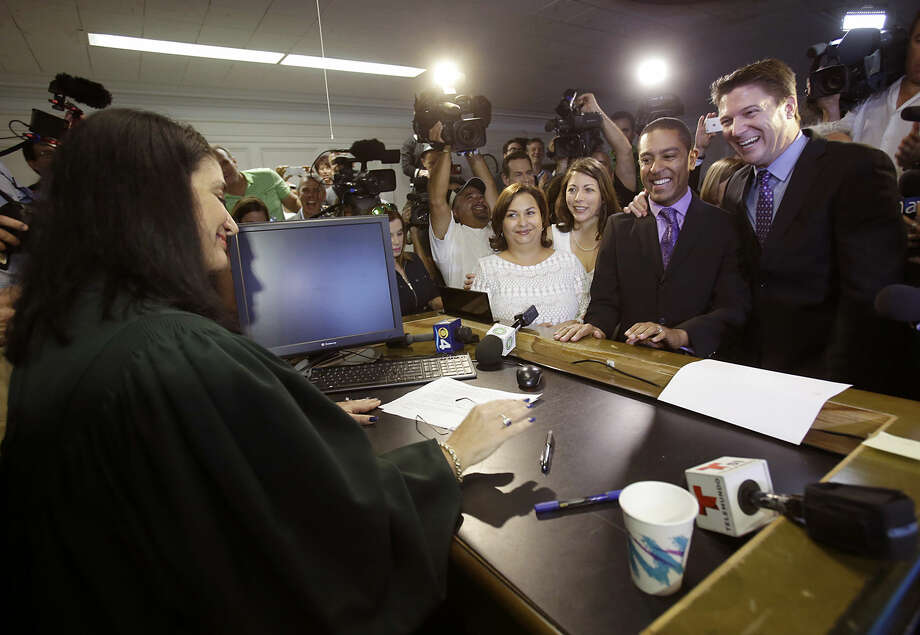 Todd Delmay, right, and his spouse, Jeff Delmay, second from right, Catherina Pareto, center, and her spouse Karla Arguello, left of center, smile after the couples were married by Miami-Dade Circuit Judge Sarah Zabel, left, Monday, Jan. 5, 2015 in Miami. Judge Zabel provided a jump-start Monday to Florida's entry as the 36th state where gays and lesbians can legally marry, saying she saw no reason why same-sex couples couldn't immediately get their licenses in Miami-Dade County ahead of a midnight launch statewide. (AP Photo/Wilfredo Lee)