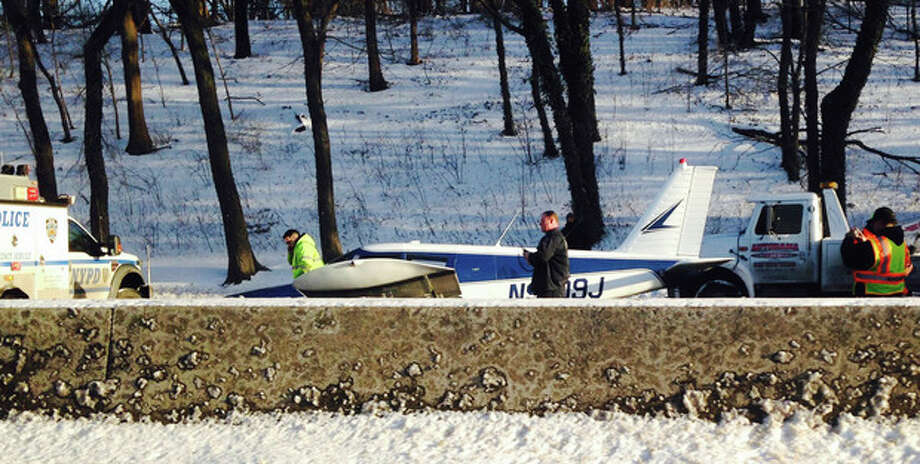 In this photo provided by Patricia Sapol, emergency personnel respond to a light airplane that made an emergency landing on the Major Deegan Expressway in the Bronx borough of New York, Saturday, Jan. 4, 2014. The Piper PA-28, set down at around 3:20 p.m. on the northbound side of the highway. Police and fire officials said neither the male pilot nor two female passengers appeared to have been badly hurt. (AP Photo/Patricia Sapol) / Patricia Sapol