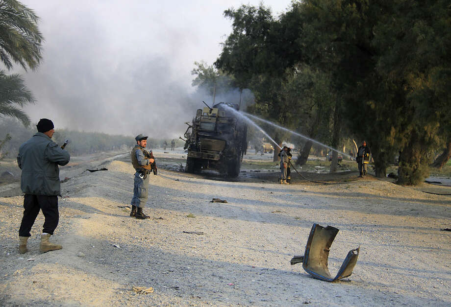 Afghan forces inspect the site of a roadside bomb explosion in Jalalabad, east of Kabul, Afghanistan, Monday, Jan. 5, 2015. A roadside bomb hit a NATO convoy in eastern Nangahar province, damaging one vehicle but inflicting no casualties, spokesman Capt. Frank Hartnett said. (AP Photo/AP Photo)