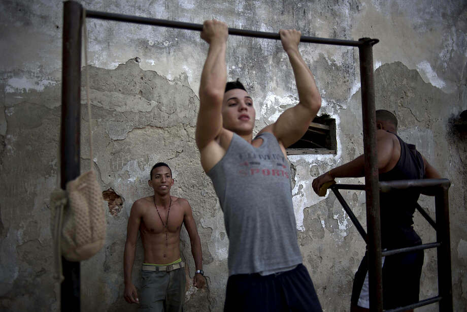 Young men work out at a community sports center in Havana, Cuba, Monday, Jan. 5, 2015. The Dec. 17 announcement of detente between the U.S. and Cuba has raised hopes of improved conditions on the island but Cubans also worry about the changes to come. (AP Photo/Ramon Espinosa)