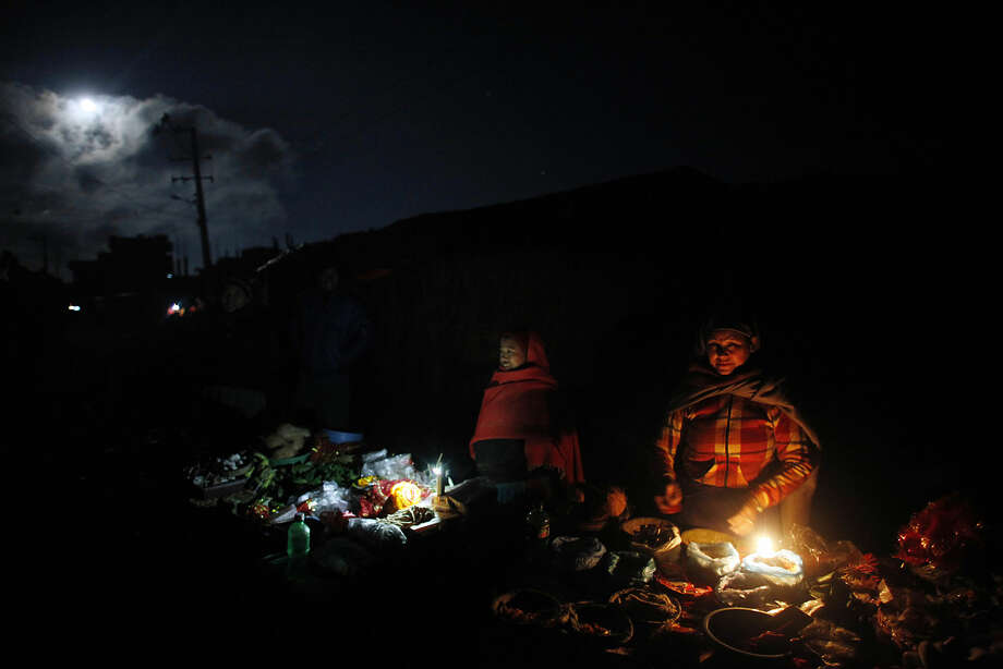 Nepalese roadside vendors wait for the customer to sell the item used for ritual during the first day Swasthani Bratakatha festival in Sankhu, on the outskirts of Katmandu, Monday, Jan. 5, 2015. During this month-long festival, devotees recite Holy Scriptures dedicated to Hindu goddess Swasthani and Lord Shiva. Unmarried women pray to get a good husband while those married pray for the longevity of their husbands by observing a month-long fast. (AP Photo/Niranjan Shrestha)