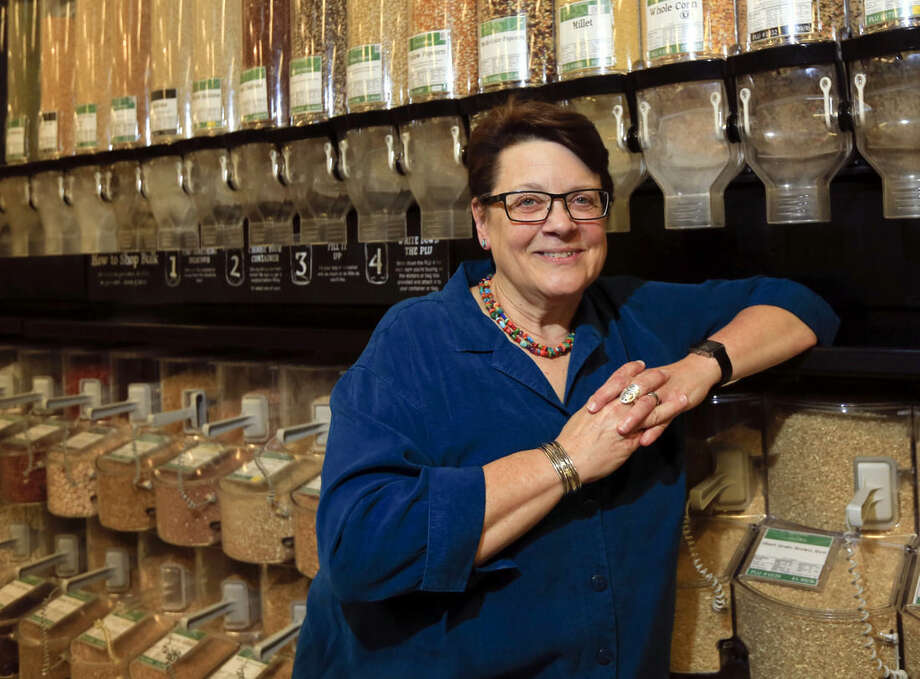 In this Tuesday, Dec. 15, 2015, photo, Deborah Dennis, acting president at Honest Weight Food Co-Op, poses at the store in Albany, N.Y. Food cooperative programs that allow members to scoop rice, sort organic vegetables and ring up sales in return for grocery discounts are fading fast. (AP Photo/Mike Groll)