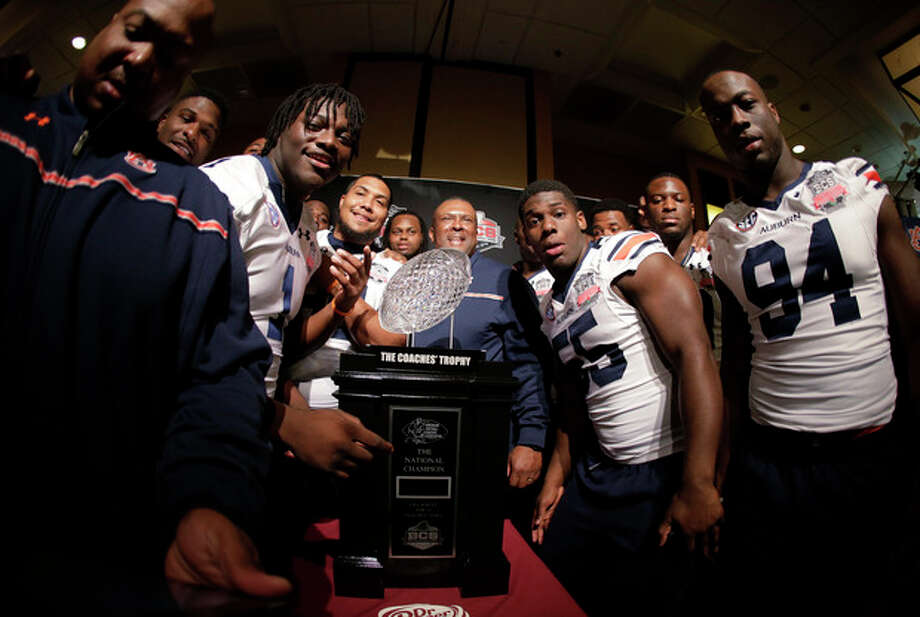 Auburn players pose with The Coaches' Trophy during media day for the NCAA BCS National Championship college football game Saturday, Jan. 4, 2014, in Newport Beach, Calif. Florida State plays Auburn on Monday, Jan. 6, 2014. (AP Photo/Chris Carlson) / AP