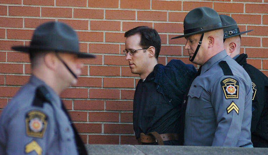 Eric Frein is led away by Pennsylvania State Police Troopers at the Pike County Courthouse after his preliminary hearing on Monday, Jan. 5, 2015, in Milford, Pa. Frein is charged with fatally shooting a Pennsylvania state trooper and wounding another during an ambush at their barracks in September. A judge ordered Frein to stand trial on the charges. Prosecutors are seeking the death penalty. Frein led authorities on a 48-day manhunt through the Pocono woods before marshals captured him at an abandoned airplane hangar. (AP Photo/Scranton Times & Tribune, Butch Comegys)