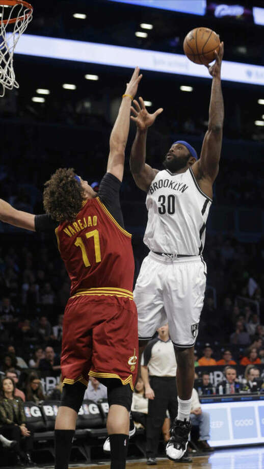 Brooklyn Nets' Reggie Evans (30) shoots over Cleveland Cavaliers' Anderson Varejao (17) during the first half of an NBA basketball game on Saturday, Jan. 4, 2014, in New York. (AP Photo/Frank Franklin II)