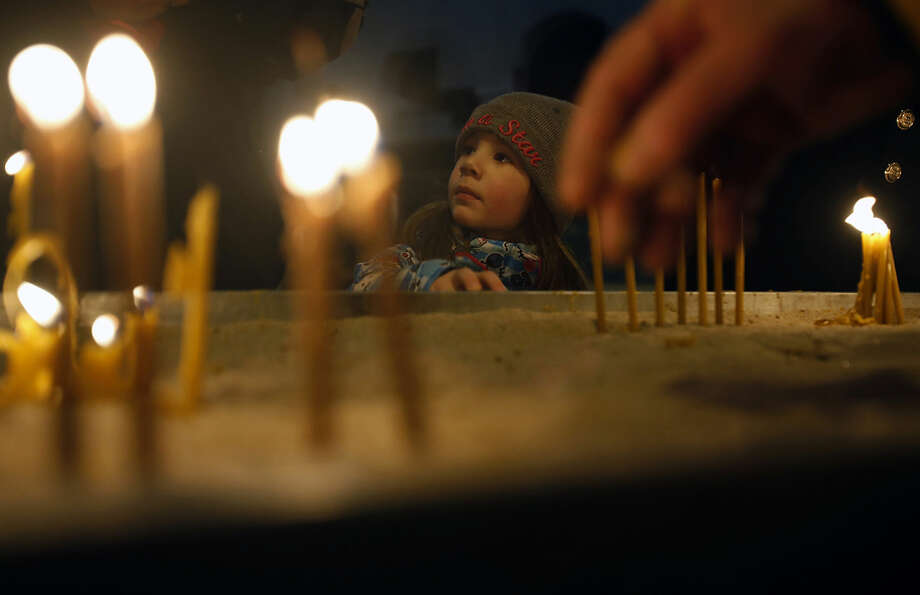 A girl watches people lighting candles in the St. Sava Serbian Orthodox temple in downtown Belgrade, Serbia, Tuesday, Jan. 6, 2015. The Serbs celebrate Christmas according to Julian Calendar, on January 7. (AP Photo/Darko Vojinovic)