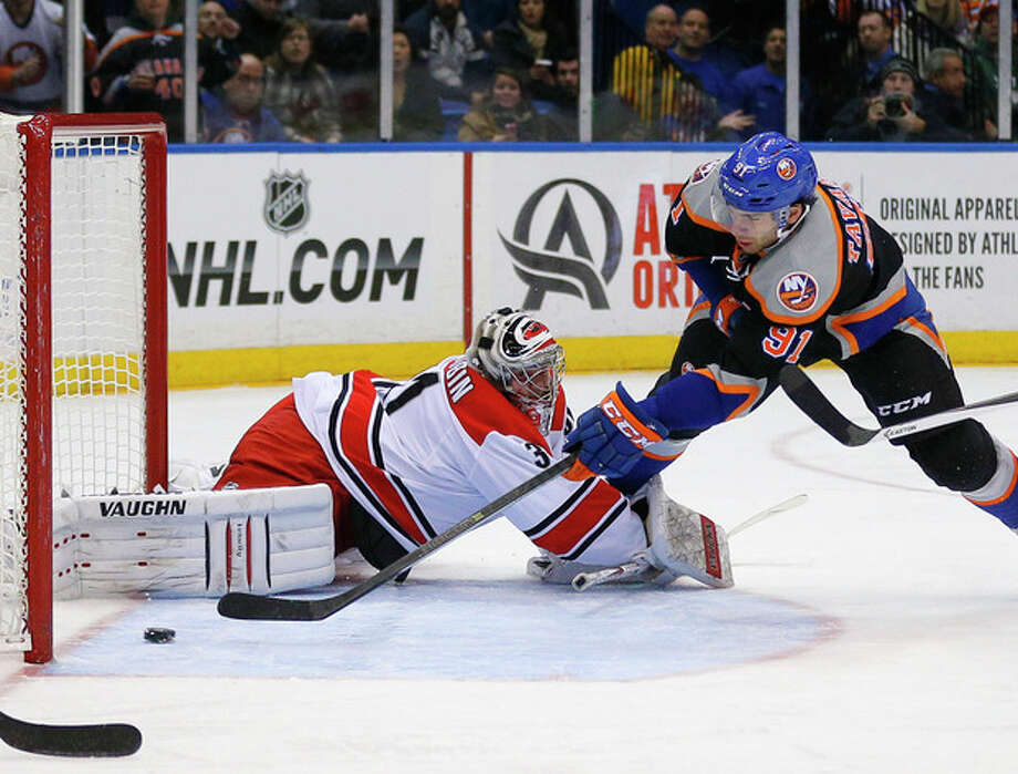 New York Islanders center John Tavares (91) scores a goal past Carolina Hurricanes goalie Anton Khudobin (31) in the second period of an NHL hockey game in Uniondale, N.Y., Saturday Jan. 4, 2014. (AP Photo/Paul J. Bereswill) / FR168017 AP