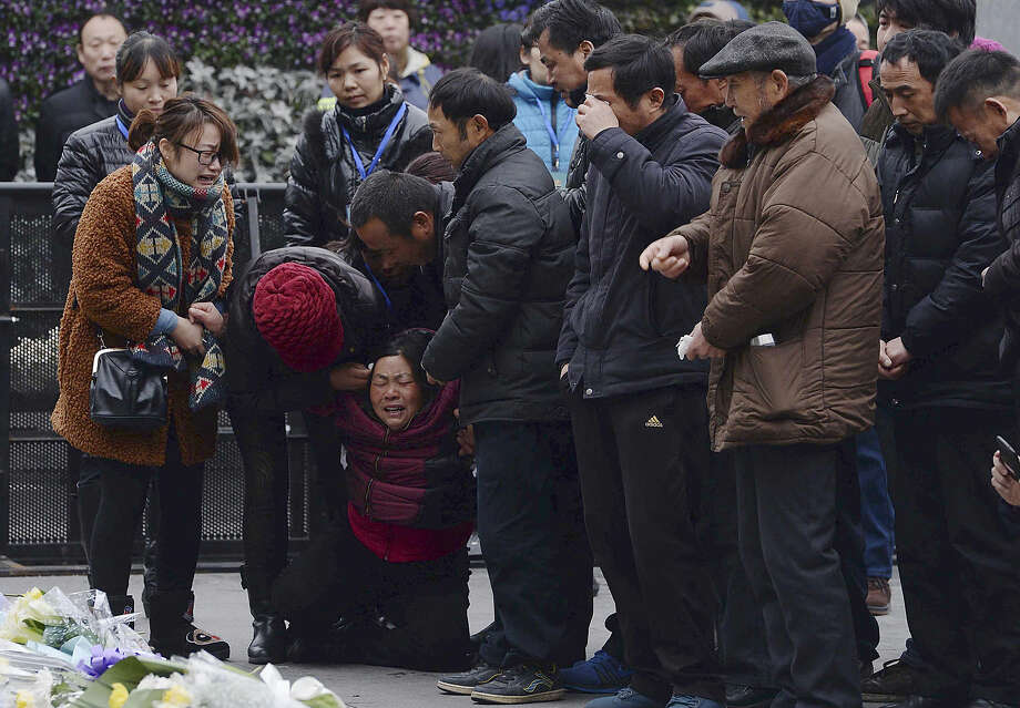A woman, third from left, grieves as she is comforted by other relatives of a New Year's Eve stampede victim at the site of the tragic accident in Shanghai, China Tuesday, Jan. 6, 2015. Some wailed and some staggered with grief as the relatives of the 36 people killed in the stampede visited the disaster site Tuesday for seventh-day commemorations that are a revered ritual in China. (AP Photo) CHINA OUT