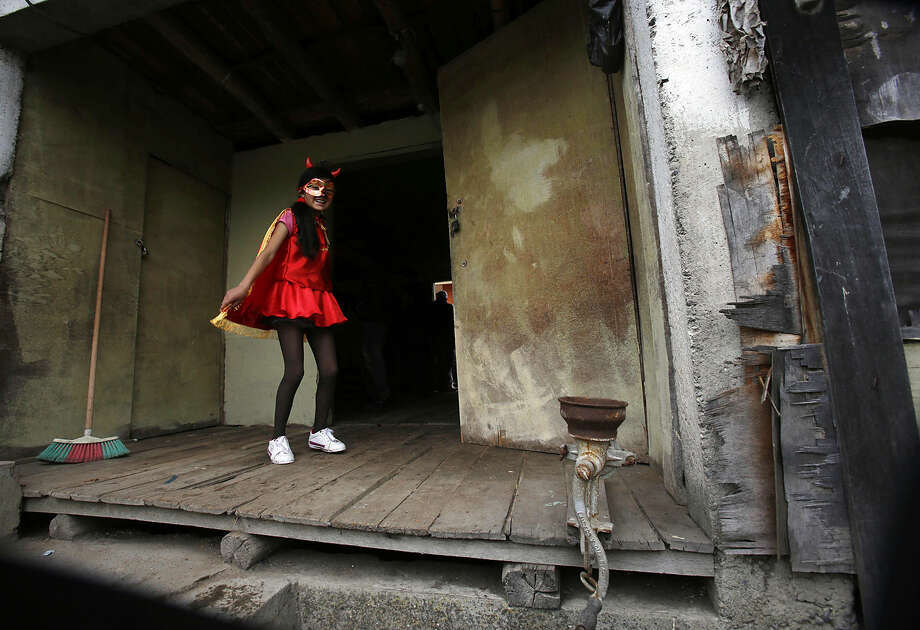 A girl practices her dance steps before participating in the traditional parade of La Diablada en Pillaro, Ecuador, Sunday, Jan. 4, 2015. Originally people dressed in devil costumes where used to open up space to allow other participants to dance, but over the years the character gained popularity and became the most popular costume of the feast. (AP Photo/Dolores Ochoa)