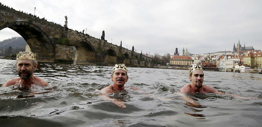 Polar swimmers take part in the traditional Three Kings swim in the Vltava River in Prague, Czech Republic, Tuesday, Jan. 6, 2015. Prague Castle and the Charles Bridge is in the background. (AP Photo/Petr David Josek)
