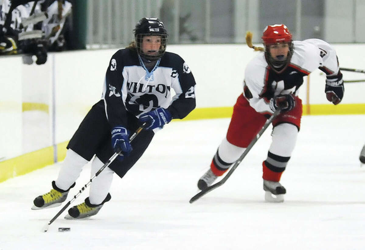 Hour photo/John Nash Wilton's Meghan Keating, left, races up the ice as Hall-Conard defender Sarah Gockel trails the play in Saturday's game at the SoNo Ice House in Norwalk.