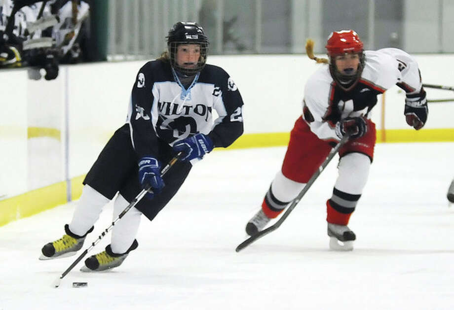 Hour photo/John NashWilton's Meghan Keating, left, races up the ice as Hall-Conard defender Sarah Gockel trails the play in Saturday's game at the SoNo Ice House in Norwalk.