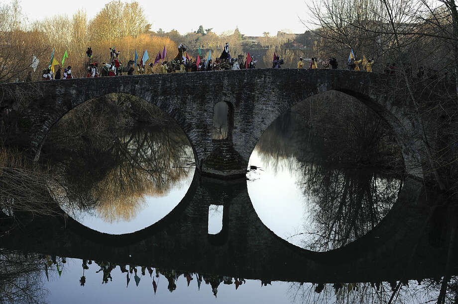 The Cabalgata Los Reyes Magos (Cavalcade of the three kings) cross Magdalena bridge over Arga River the day before Epiphany, in Pamplona, northern Spain, Monday, Jan. 5, 2015. It is a parade symbolizing the coming of the Magi to Bethlehem following the birth of Jesus. In Spain and many Latin American countries Epiphany is the day when gifts are exchanged. (AP Photo/Alvaro Barrientos)