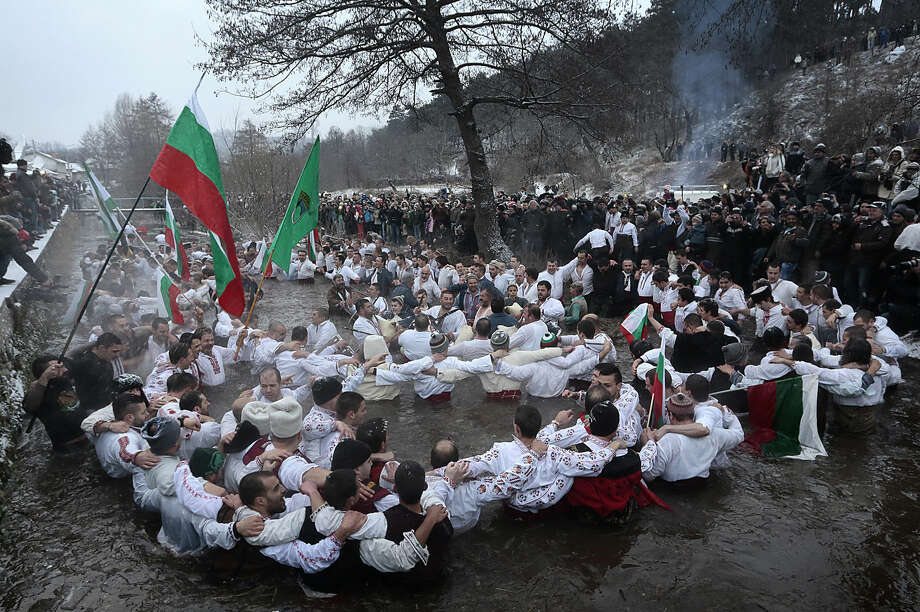 Believers sing and dance in the icy water of the river Tundzha as they celebrate Epiphany day, a Christian festival, in the town of Kalofer, Bulgaria, Tuesday, Jan. 6, 2015. Traditionally, an Eastern Orthodox priest throws a cross in the river and it is believed that the one who retrieves it will be healthy through the year. (AP Photo/Valentina Petrova)
