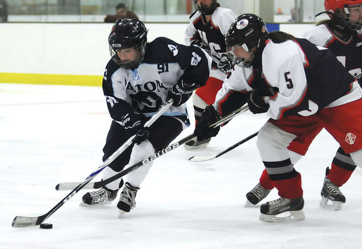 Hour photo/John Nash Wilton's Emilie Arrix, left, protects the puck from Hall-Conard defender Melanie Newton during Saturday's game at the SoNo Ice House in Norwalk.