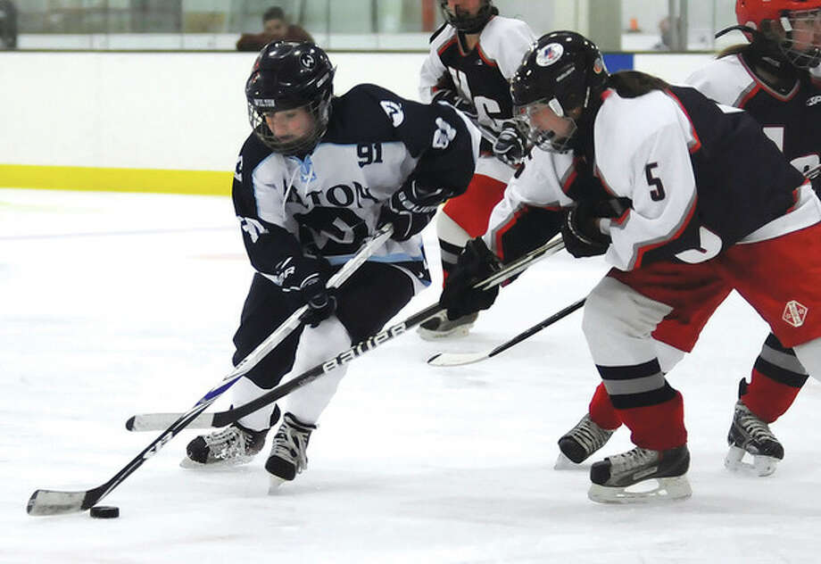 Hour photo/John NashWilton's Emilie Arrix, left, protects the puck from Hall-Conard defender Melanie Newton during Saturday's game at the SoNo Ice House in Norwalk.