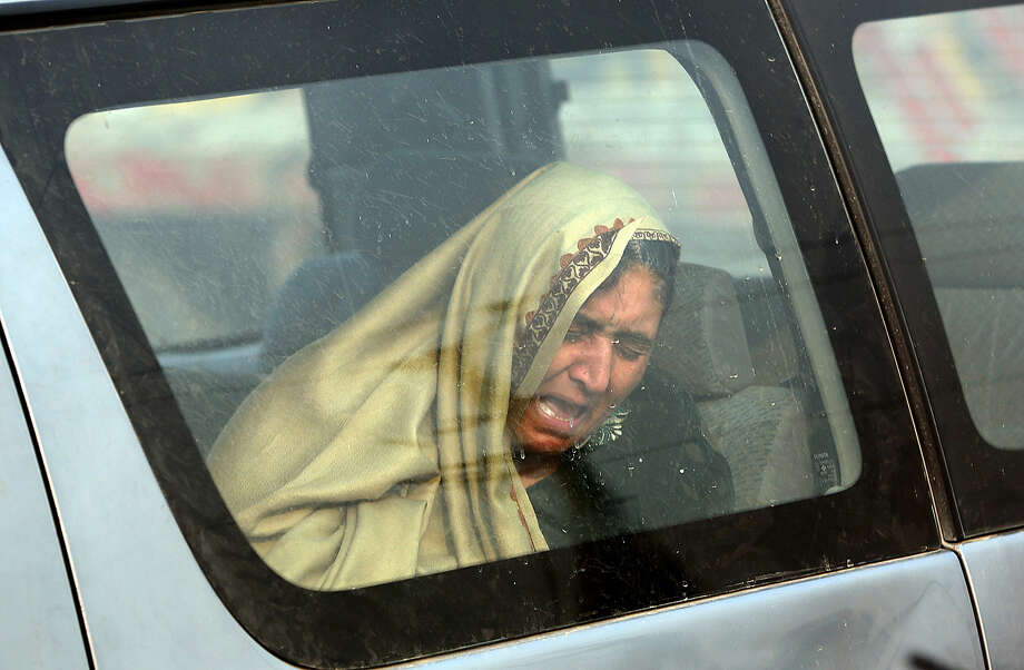An Afghan woman cries at the site of a suicide attack in Kabul, Afghanistan Monday, Jan. 5, 2015. The bomber has struck near the headquarters of the European police training mission in Kabul, killing one Afghan civilian and wounding several others nearby. (AP Photo/Massoud Hossaini)