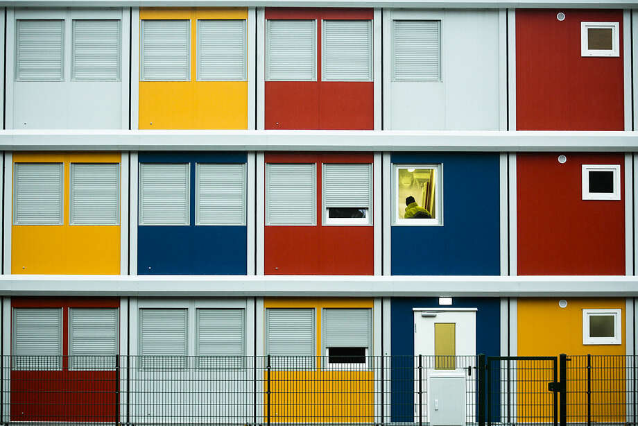 A construction worker walks up the staircase of a so-called container village for refugees which is partially under construction in the district of Koepenick in Berlin, Monday, Jan. 5, 2015. The containers were built as temporary living quarters for the rising numbers of refugees applying for asylum in the German capital. (AP Photo/Markus Schreiber)