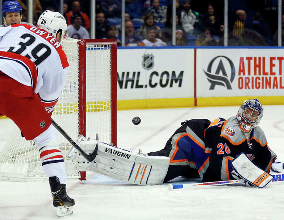 New York Islanders goalie New York Islanders goalie Evgeni Nabokov (20) watches as Carolina Hurricanes right wing Patrick Dwyer (39) shoots past the empty net during the first period of an NHL hockey game on Saturday Jan. 4, 2014, in Uniondale, N.Y. (AP Photo/Paul J. Bereswill) / FR168017 AP