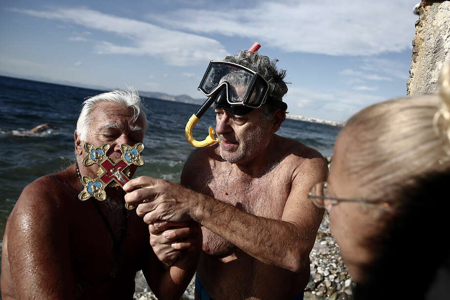 Nikos Konstantopoulos holds a cross as a swimmer kisses it, after a competition to retrieve it from the water during a ceremony to bless the water in Greece's Flisvos beach, at Paleo Faliro near Athens on Monday, Jan. 6, 2015. Similar ceremonies to mark Epiphany were held across Greece on river banks, seafronts and lakes. An Orthodox priest throws a cross into the water and swimmers race to be the first to retrieve it. (AP Photo/Petros Giannakouris)