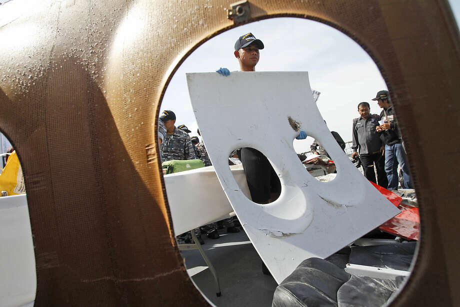 A crew member of Indonesian Navy ship KRI Bung Tomo holds a piece of the window panel of AirAsia Flight 8501 recovered in search operations for the ill-fated jetliner, during a press conference at the Navy's Eastern Fleet Naval Base in Surabaya, East Java, Indonesia, Monday, Jan. 5, 2015. The Singapore-bound plane crashed into the Java Sea 42 minutes after taking off on Dec. 28. (AP Photo/Trisnadi)