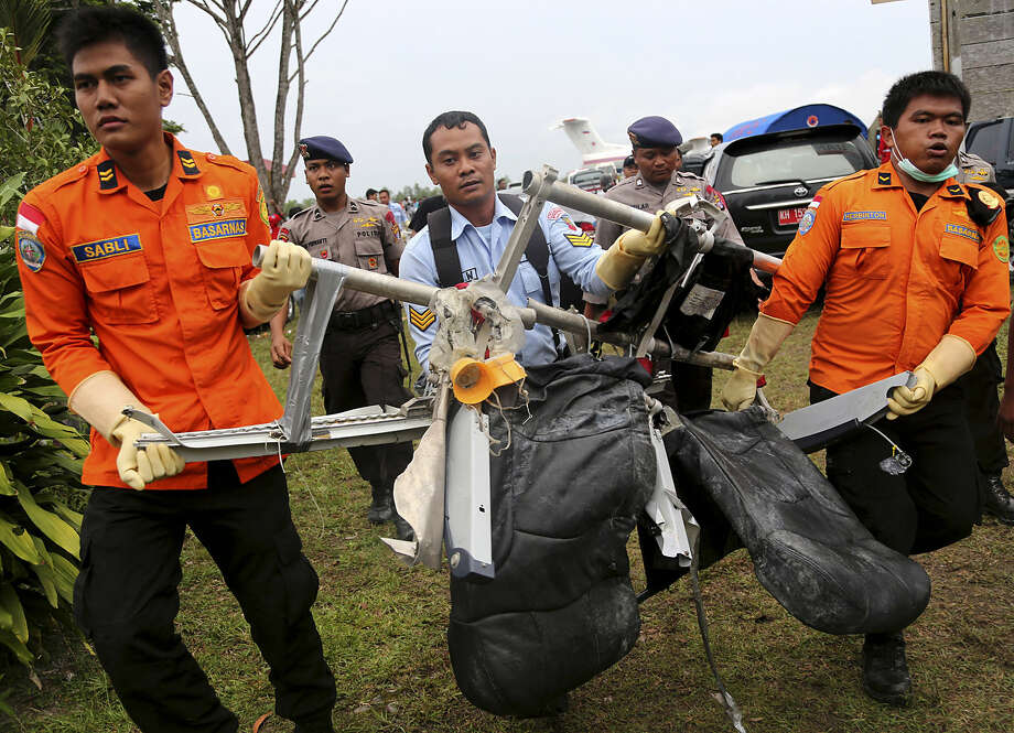 National Search and Rescue Agency personnel carry the seats of AirAsia Flight 8501 after being airlifted by a U.S. Navy helicopter, at the airport in Pangkalan Bun, Indonesia, Monday, Jan. 5, 2015. At least five ships with equipment that can detect pings emitted by flight data and cockpit voice recorders are on station and the weather has improved in the search for the AirAsia jet that crashed a week ago. (AP Photo/Tatan Syuflana)