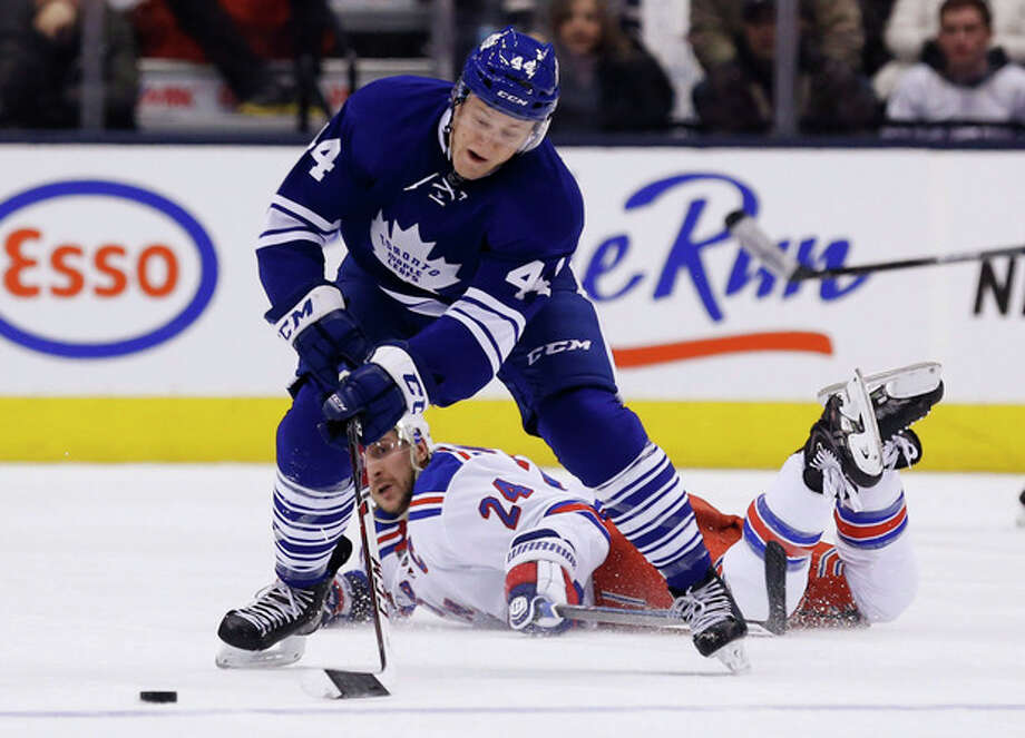 New York Rangers' Ryan Callahan falls as Toronto Maple Leafs' Morgan Rielly controls the puck during the first period of an NHL hockey game in Toronto, Saturday, Jan. 4, 2014. (AP Photo/The Canadian Press, Mark Blinch) / The Canadian Press