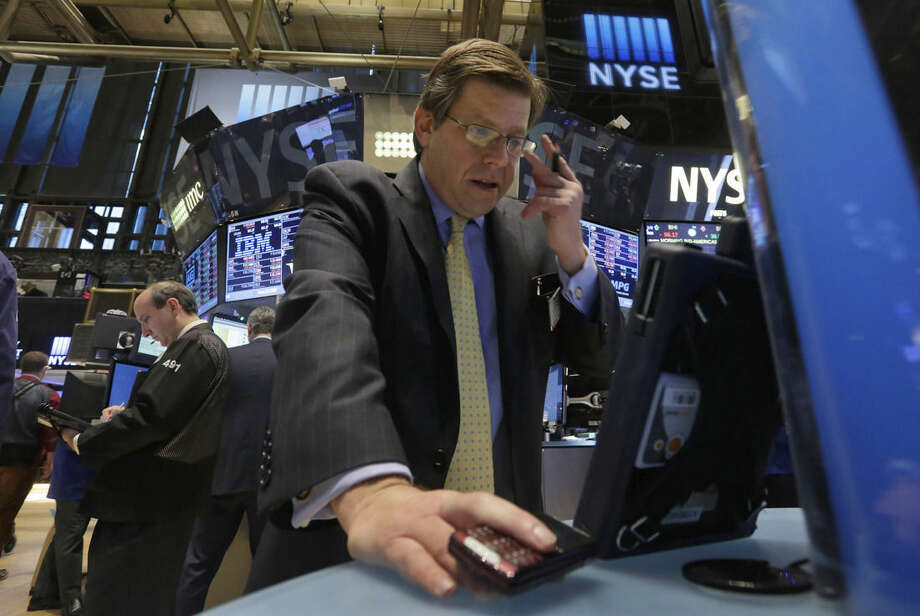 Trader Edward Schreier, right, works on the floor of the New York Stock Exchange Monday, Jan. 5, 2015. US stocks opened lower Monday, led by declines in energy stocks as the price of oil plunged again. (AP Photo/Richard Drew)