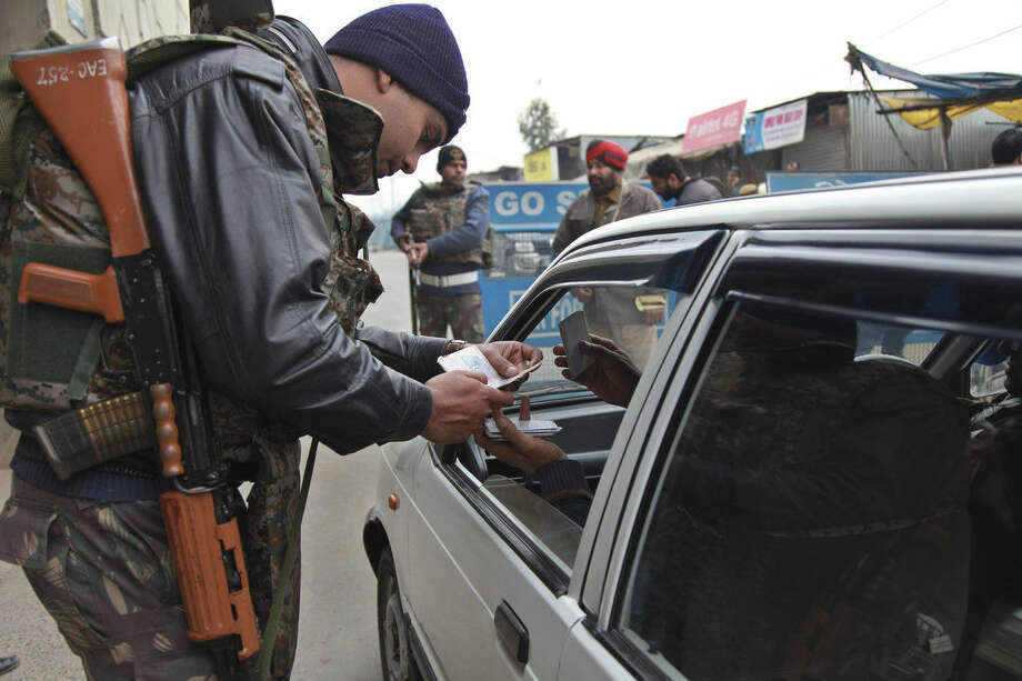 Indian security personnel check people entering an airbase in Pathankot, India, Monday, Jan. 4, 2016. After saying all the gunmen who attacked the Indian airbase near the Pakistan border were dead, Indian officials said at least two attackers remained and vowed to kill them Monday to end a more than 48-hour siege. (AP Photo/Channi Anand)
