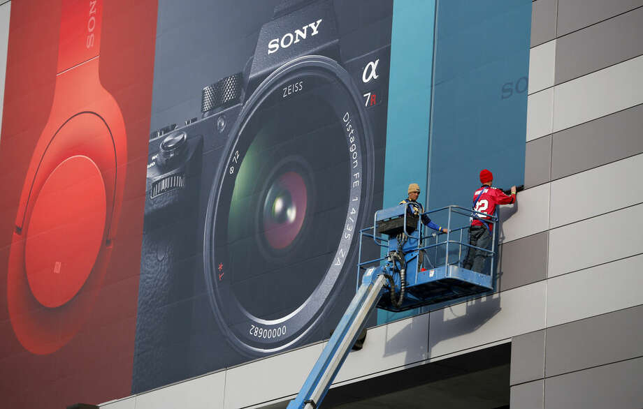 Workers install a sign for Sony products in preparation for the International CES gadget show Sunday, Jan. 3, 2016, in Las Vegas. The show officially kicks off Wednesday, Jan. 6. (AP Photo/John Locher)