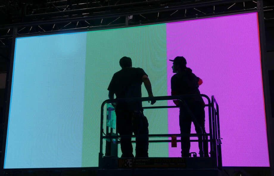 Workers install a monitor in preparation for the International CES gadget show Sunday, Jan. 3, 2016, in Las Vegas. The show officially kicks off Wednesday, Jan. 6. (AP Photo/John Locher)